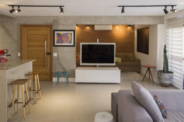 Sala de TV integrada com painel giratório Projeto de Galpão Design