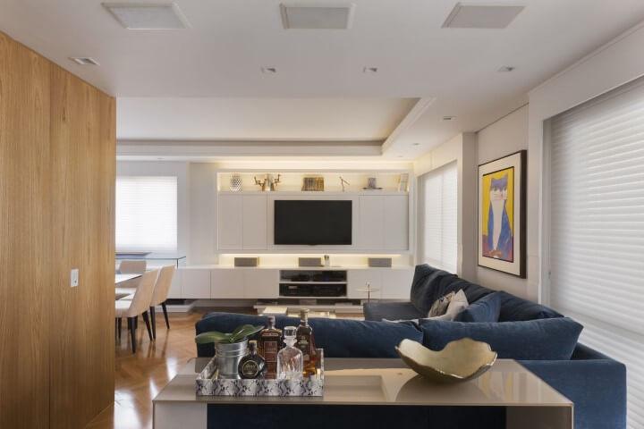 Sala de TV integrada com sala de janta e sofá em L azul Projeto de Gustavo Motta