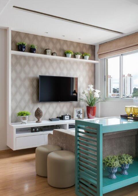 Sala de TV neutra com móvel turquesa atrás do sofá Projeto de Cláudia Comparin