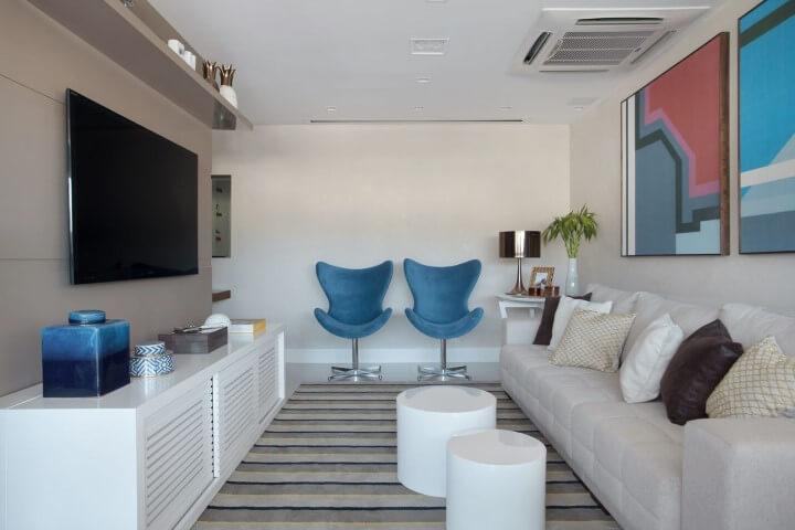 Sala de TV com móveis grandes brancos e toque coloridos Projeto de Mariana Martini
