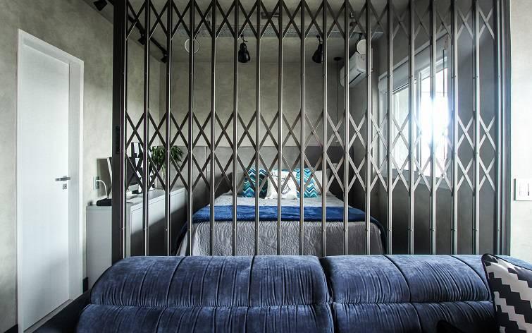 Uma porta pantográfica de ferro separa a sala do quarto. Pode permanecer aberta ou fechada, conforme a necessidade.