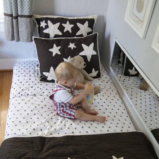 Quarto montessoriano com espelho atrás da cama