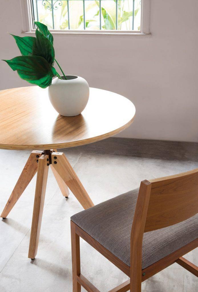 Mesa Tabuleiro, de Fernando Jaeger, com pés em madeira maciça conectados ao tampo por uma haste central de aço.