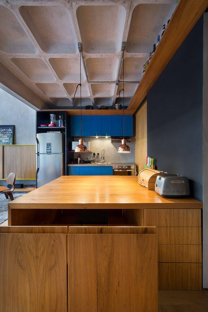 Na cozinha, as cadeiras retráteis, da grande mesa, são um elemento que economizam espaço quando fechadas.