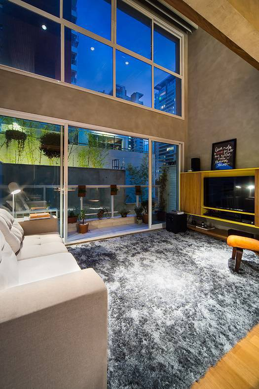 7 Uma grande parede com janelas de vidro promovem a integração entre o dentro e o fora da morada, dando a sensação de amplitude. Quando aberto, o móvel da parede exibe uma grande TV, desejo dos moradores.