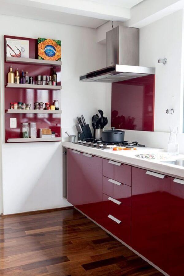 A cozinha vermelha se conecta com o piso de madeira