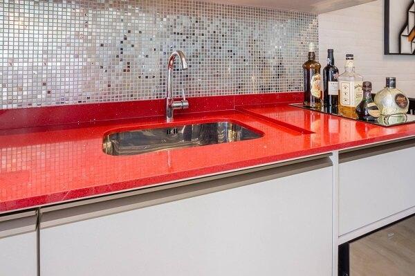 A pia da cozinha vermelha se destaca na decoração do ambiente