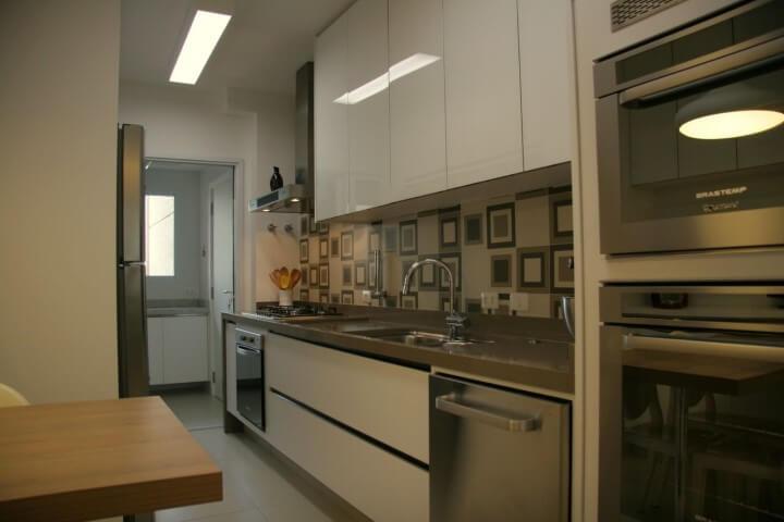 Armário de cozinha de parede branco em ambientes integrados Projeto de Moussi Arquitetura