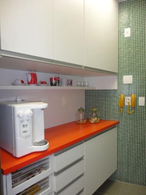Cozinha planejada com armário de cozinha de parede branca e bancada laranja Projeto de Maria Helena Torres