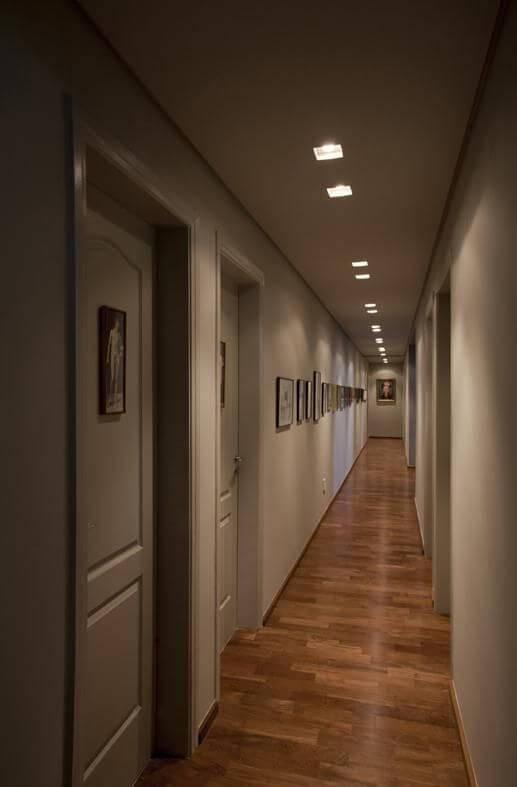 Corredor longo com piso de madeira e iluminação embutida Projeto de AMC Arquitetura