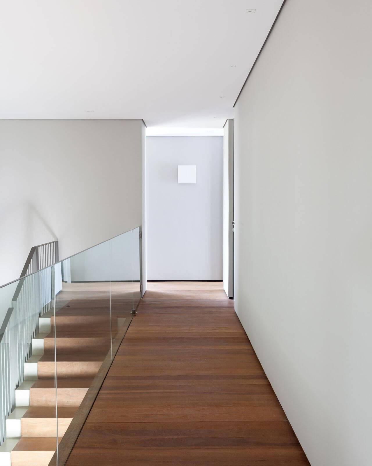 Corredor com piso de madeira e parte dos degraus da escada Projeto de Consuelo Jorge
