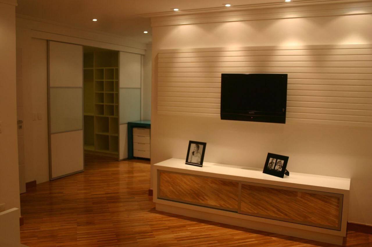 Sala com piso de madeira com rack espelhado Projeto de Sueli Porwjan