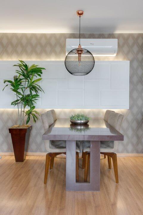 Sala de jantar com piso de madeira e papel de parede de losango Projeto de Claudia Comparin