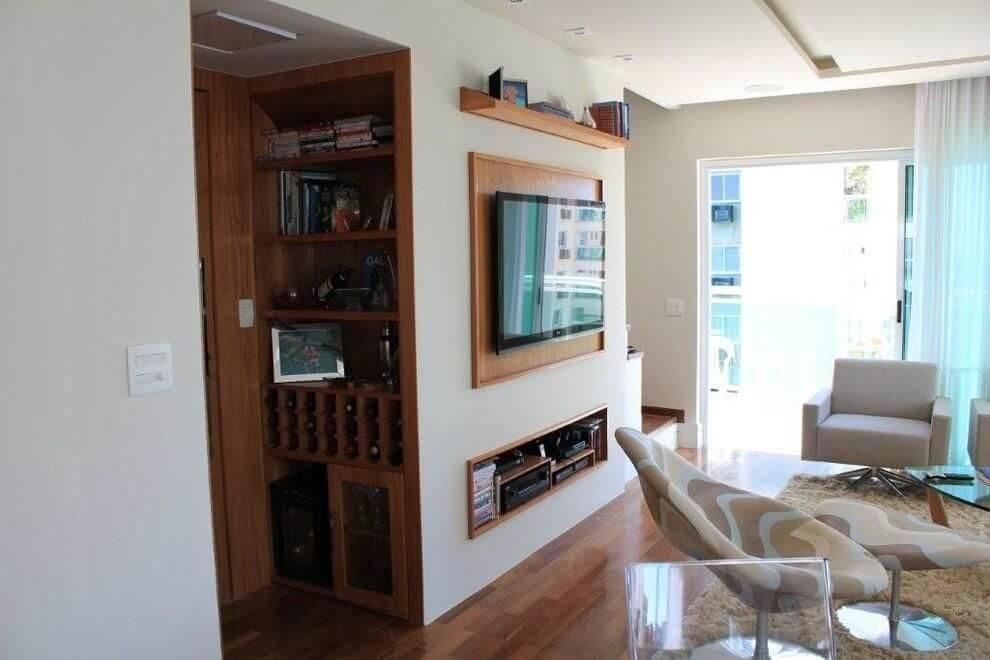 Sala de estar com piso de madeira e cantinho com adega Projeto de BL Arquitetura