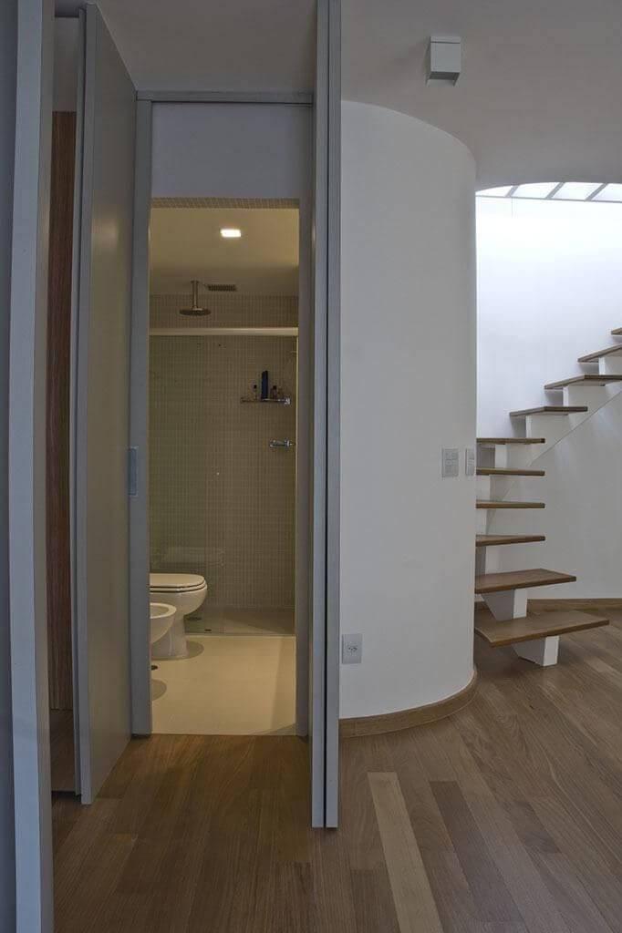 Sala com piso de madeira e escada com degraus do mesmo material Projeto de Arquiteto Donini