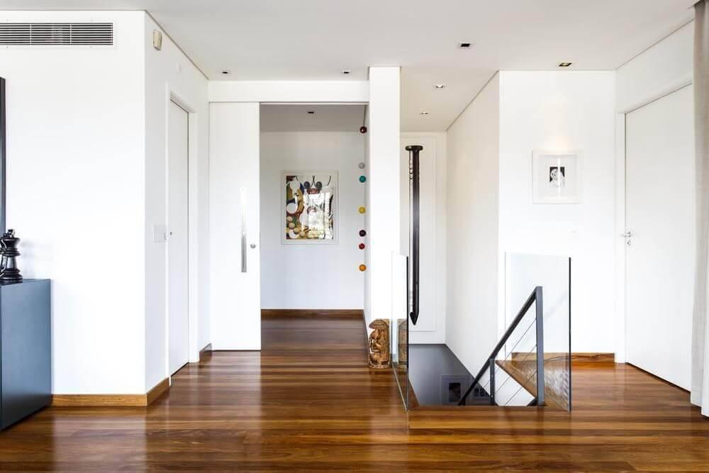 Corredor com piso de madeira escuro Projeto de Paula Bittar
