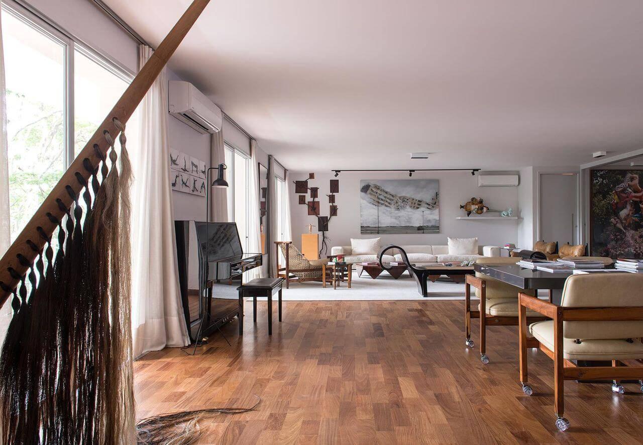 Sala com metade do piso de madeira e metade com piso diferente dividindo ambientes Projeto de AMC Arquitetura