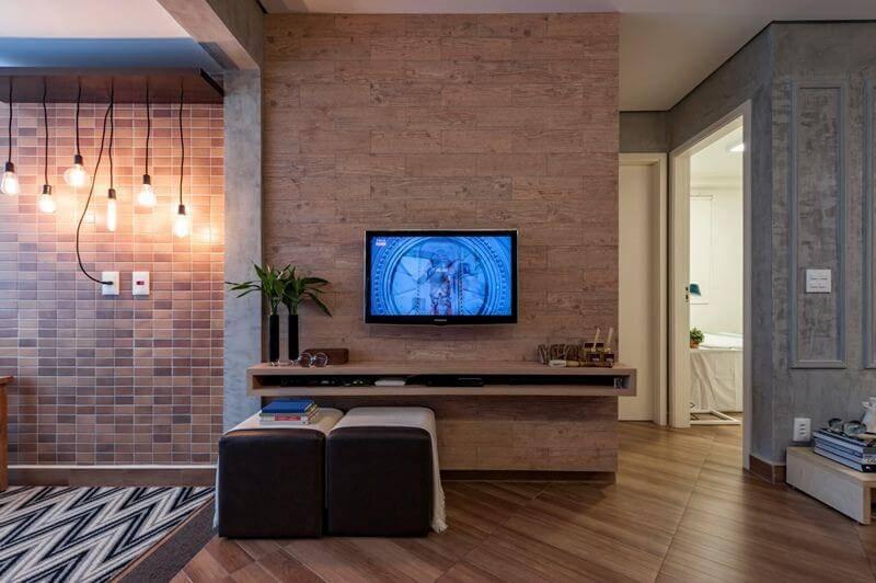 Sala com parede textura de pedra e piso de madeira Projeto de MIS Arquitetura