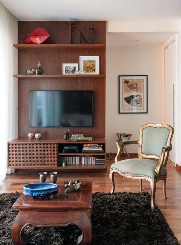 Sala de estar com piso de madeira e painel de madeira para TV Projeto de MIS Arquitetura