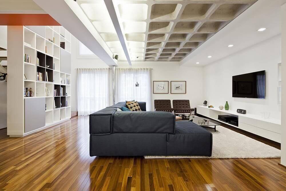 Sala de TV ampla com pio de madeira em tons diferentes de marrom Projeto de Stuchie Leite