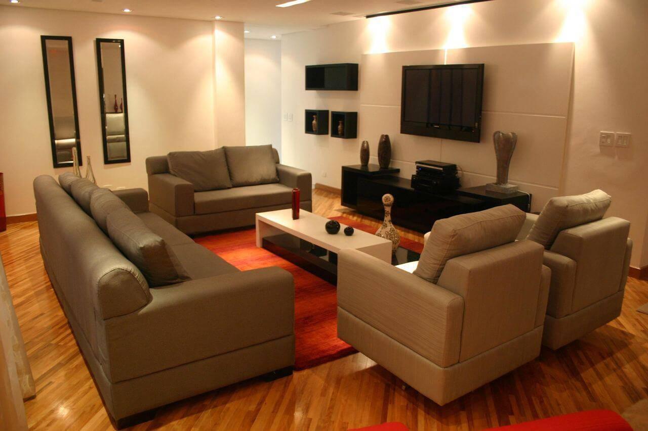 Sala de TV com iluminação confortável e piso de madeira Projeto de Sueli Porwjan