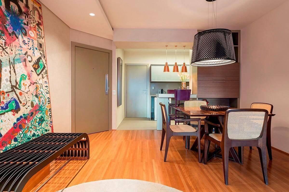 Sala de jantar com piso de madeira e quadro grande na parede Projeto de Denise Barretto