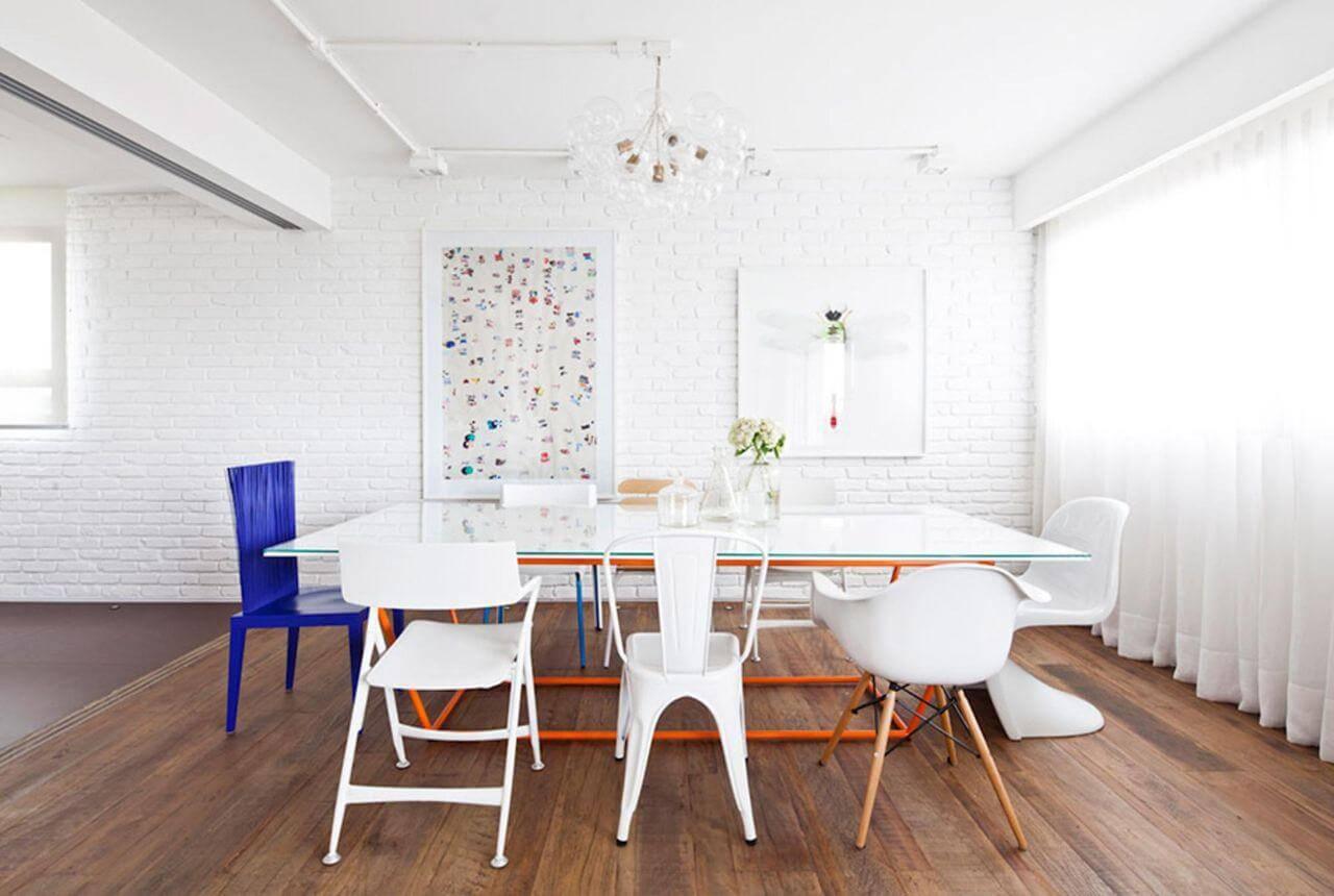 Sala de jantar moderna com cadeiras diferentes e piso de madeira assoalho Projeto de Flávia Gerab Tayar