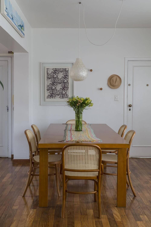 Sala de jantar com piso de madeira e mesas e cadeira do mesmo material Projeto de Leila Dioniz