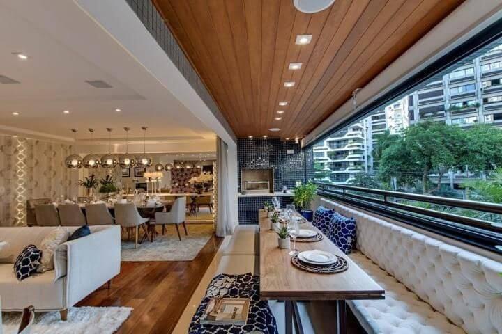 Ambiente sofisticado integrado com piso de madeira e revestimento de madeira no teto Projeto de Carla Felippi