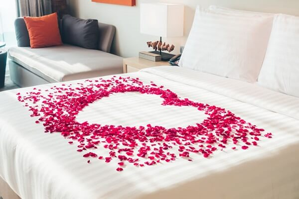 Para o dia dos namorados decore a cama com pétalas de rosas