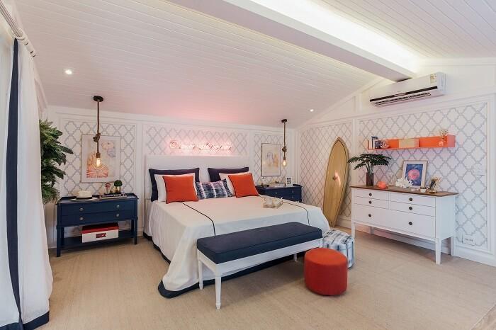 A prancha de surf de madeira se destaca na decoração desse quarto de casal