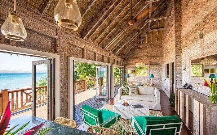 As portas de vidros facilitam a visão da paisagem na casa de praia