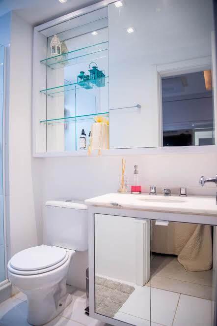 Lavabo com prateleiras de vidro e espelho para banheiro em formato de espelheira Projeto de Roberta Menna Barreto