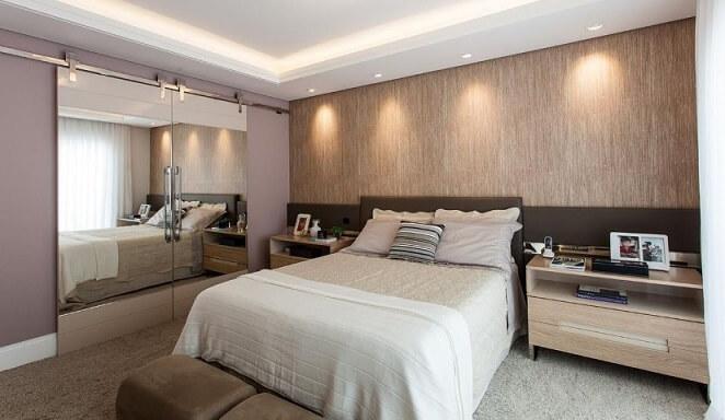 Quarto de casal com textura de parede atrás da cama Projeto de Juliana Pippi