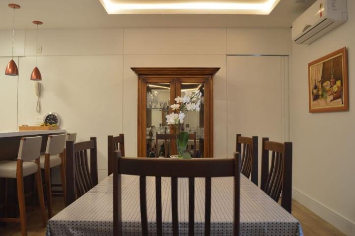 Sala de jantar com sanca de gesso e iluminação embutida sobre a mesa Projeto de Marina Angeloni