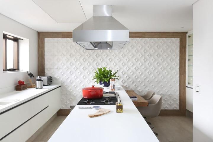 Cozinha branca com revestimento 3D em toda a parede com borda de madeira Projeto de Patricia Bergantin