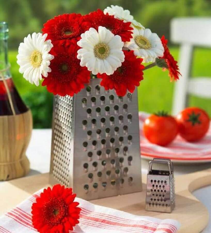 Decoração de chá de panela com arranjo de flores em suporte de ralador