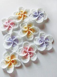 Flor de crochê brancas com centros coloridos