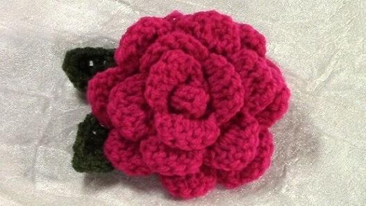 Flor de crochê rosa com folha verde escura