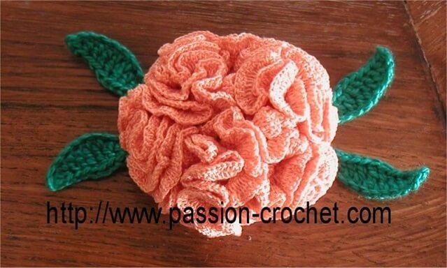 Flor de crochê rosa com folhas verdes