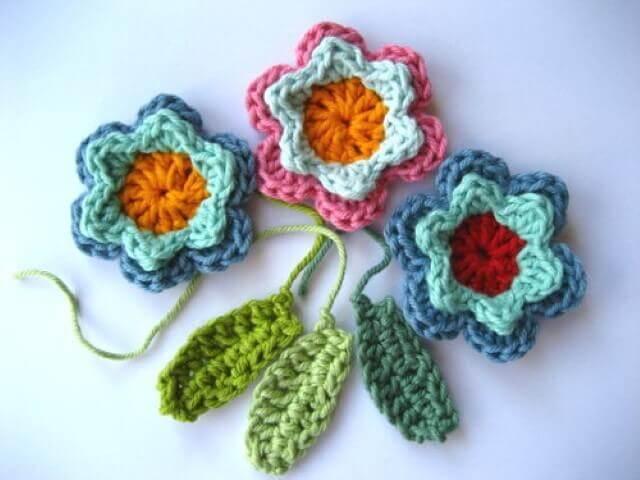 Flores de crochê coloridas com folhas