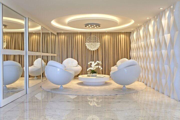 Sala de estar clara com parede com revestimento 3D branco Projeto de Iara Kilaris