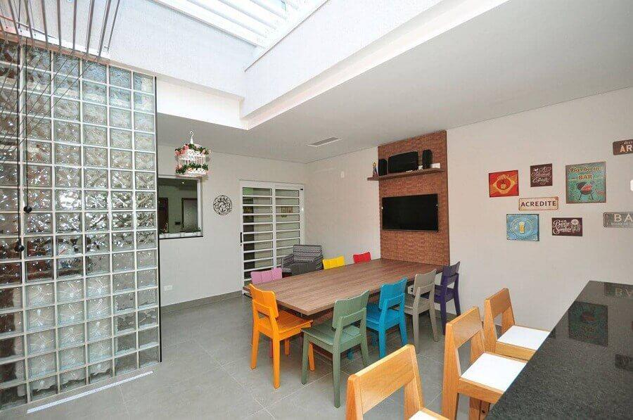 cozinha ampla decorada com cadeiras coloridas e cobogó de vidro Foto Condecorar
