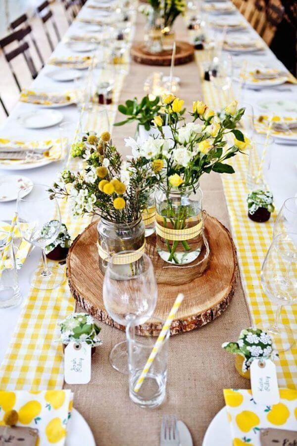 Enfeite de mesa com madeira e flores amarelas