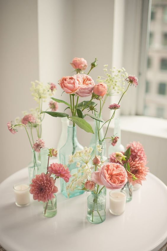 Garrafas coloridas com flores cor de rosa
