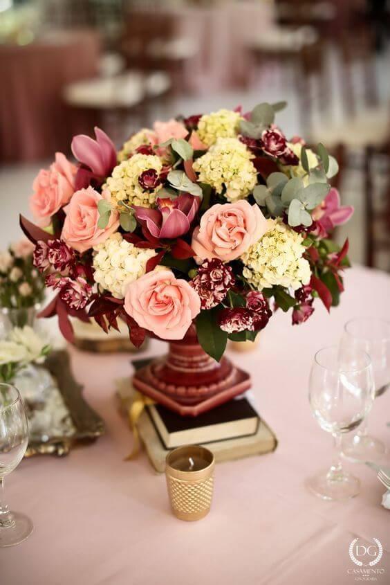 Enfeites de mesa com flores e livros