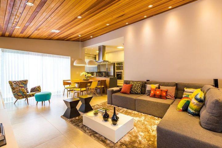 mesa de madeira - teto com ripas de madeira e poltrona com estampa
