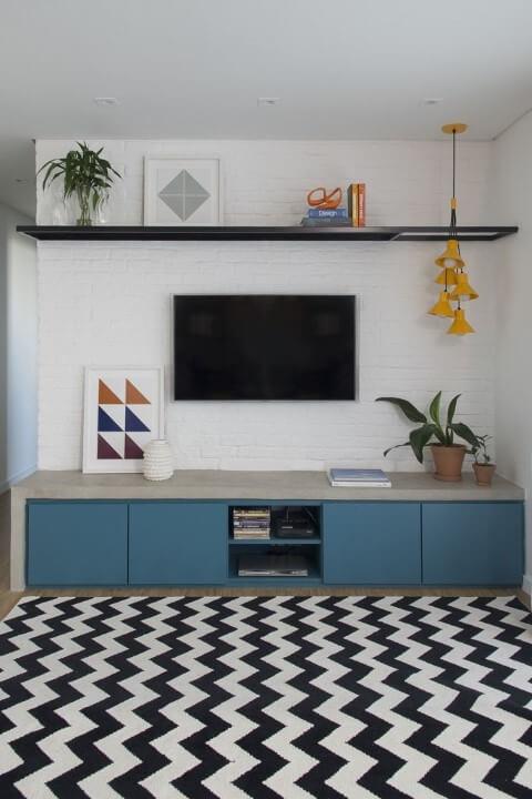 Rack para sala azul com cimento queimado e tapete chevron Projeto de SP Estúdio