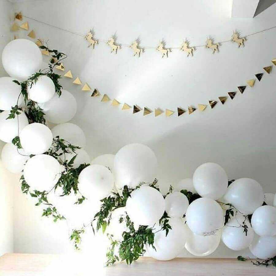 decoração minimalista para chá de bebê com arranjo de bexigas brancas com ramos de plantas e varal de unicórnios Foto Allegro