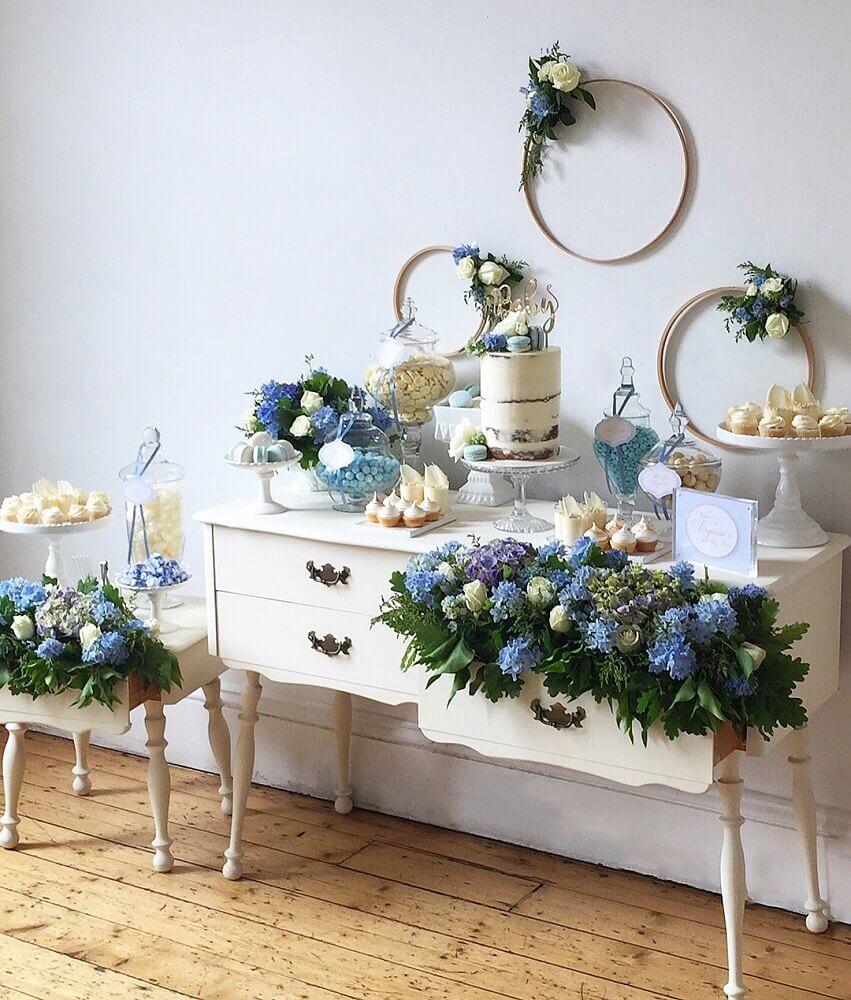 decoração simples para chá de bebê com arranjos de flores brancas e azuis Foto Buffets by Design